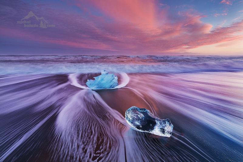 Photo: michalbalada.com;link: https://www.michalbalada.com;desc: Západ slunce na ledovcové pláži, Island. Čas přílivu a odlivu je další užitečná informace pro správné načasování, ve Windy je k nalezení pod POI, více vrstev, předpověď přílivu.;